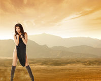 A young and sexy brunette on a desert background Stock Images