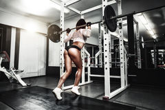 Young brunette girl in the gym doing squat with barbell Royalty Free Stock Photos