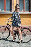 Young brunette girl with old retro style vintage bicycle Royalty Free Stock Photography