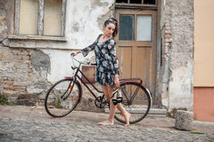 Young brunette girl with old retro style vintage bicycle Royalty Free Stock Image