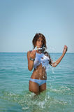 Young brunette girl in white bikini and wet t-shirt playing in the water Royalty Free Stock Photos
