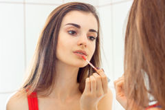 Young Sexy brunette looks in the mirror and paint lip gloss. Close-up Stock Photos