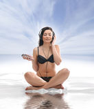 A young and sexy brunette is meditating with music Royalty Free Stock Image