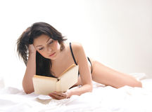 A young and sexy brunette reading on the bed Stock Photo