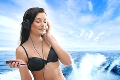 A young and sexy brunette is relaxing with music Royalty Free Stock Images