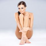 Young sexy brunette sitting while isolated Royalty Free Stock Images