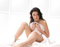 A young and sexy brunette is sitting on a silk bed Royalty Free Stock Photos
