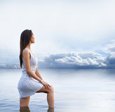 A young and sexy brunette is standing in the water Royalty Free Stock Photography