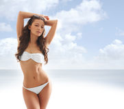 Young sexy brunette in a white swimsuit Royalty Free Stock Photos