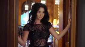 Young brunette woman in black evening dress opens the doors. And going out. Slowmotion. In bar, restaurant or hotel lobby. Luxury stock footage