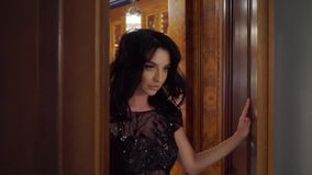 Young brunette woman in black evening dress opens the doors. And going out. Slowmotion. In bar, restaurant or hotel lobby. Luxury stock video