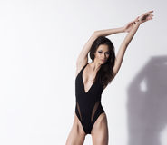A young and sexy brunette woman in a black swimsuit Royalty Free Stock Image