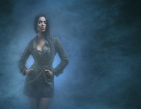 A young and sexy brunette woman on a foggy background. A young and beautiful brunette Caucasian woman posing in black clothes. The image is taken on a smoky Royalty Free Stock Images