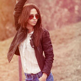 Young sexy brunette woman in jeans, jacket and sunglasses posing Stock Photo