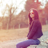 Young sexy brunette woman in jeans, jacket and sunglasses posing Stock Image