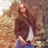 Young sexy brunette woman in jeans, jacket and sunglasses posing Royalty Free Stock Photography