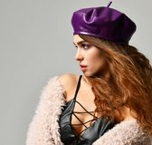 Young brunette woman in purple beret hat looking at the corner stock images