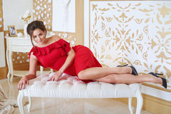 Young brunette woman in red dress lying on bed. Royalty Free Stock Photo