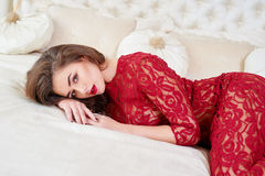 Young brunette woman in red dress lying on bed. Royalty Free Stock Photos