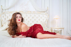 Young brunette woman in red dress lying on bed. Royalty Free Stock Image