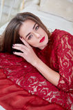 Young sexy brunette woman in red dress lying on bed. Stock Image