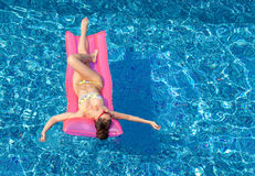 Young sexy brunette woman tanning on inflatable mattress in pool Stock Images