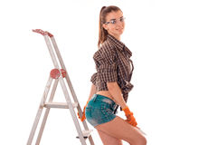 Young sexy brunette woman in uniform makes renovation with ladder looking at the camera and smiling isolated on white Royalty Free Stock Photography