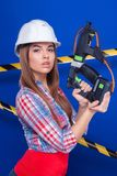 Young sexy builder girl in chechered shirt, white helmet and jea. Isolated on blue, attractive sexy brunette caucasian builder girl in chechered shirt, snickers Royalty Free Stock Photography