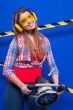 Young sexy builder girl in chechered shirt, yellow earmuffs and. Isolated on blue, attractive sexy brunette caucasian builder girl in chechered shirt, snickers Royalty Free Stock Photos