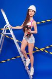 Young sexy builder girl in white top, denim shorts and helmet st. Isolated on blue, attractive brunette caucasian builder girl in denim shorts, white snickers Royalty Free Stock Photography