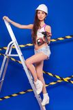 Young sexy builder girl in white top, denim shorts and helmet st. Isolated on blue, attractive brunette caucasian builder girl in denim shorts, white snickers Stock Images