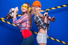 Young sexy builder girls in chechered shirts, one girl with dril Royalty Free Stock Photo