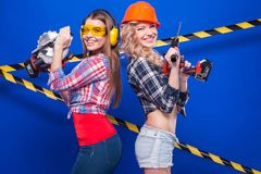 Young sexy builder girls in chechered shirts, one girl with dril Stock Photos