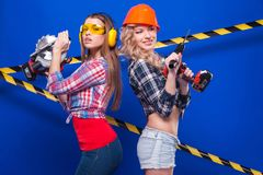 Young sexy builder girls in chechered shirts, one girl with dril Stock Image