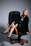 The young sexy  business woman. Is shown sitting in office armchair Stock Image