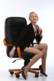 The young sexy  business woman. Is shown sitting in office armchair Royalty Free Stock Photography