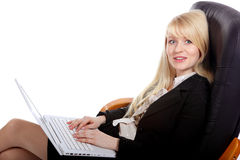 The young sexy  business woman. The young blonde the business woman sits in armchair and holds a computer Royalty Free Stock Photography