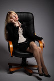 The young sexy  business woman. Is shown sitting in office armchair Royalty Free Stock Photo