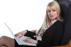 The young sexy  business woman. The young blonde the business woman sits in armchair and holds a computer Royalty Free Stock Images