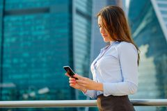 Young sexy business woman with smart phone on the modern city background Stock Image