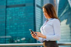 Young sexy business woman with smart phone on the modern city background Stock Photo