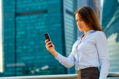 Young sexy business woman with smart phone on the modern city background Royalty Free Stock Photos