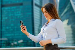 Young sexy business woman with smart phone on the modern city background Stock Photos