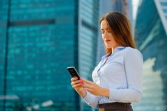 Young sexy business woman with smart phone on the modern city background Royalty Free Stock Photography