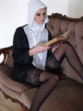 A young and sexy Caucasian nun reading the bible Royalty Free Stock Photo