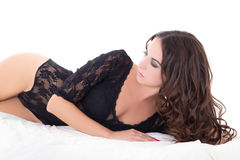 Young sexy charming woman in black lace lingerie lying on bed is Stock Photo