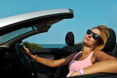 Young chic woman with sunglasses driving cabr stock photo