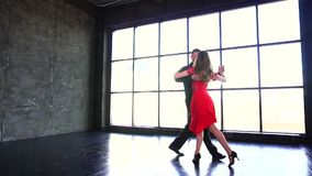 Young couple dancing tango. Professional girl in red dress and man dancing latin. A modern studio.