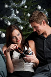 Young sexy couple in front of Christmas tree Royalty Free Stock Photography