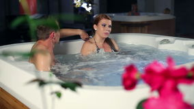 Young sexy couple in jacuzzin having conversation stock video